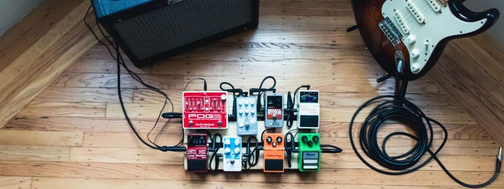 Delay and other pedals on a pedal board in a practice room