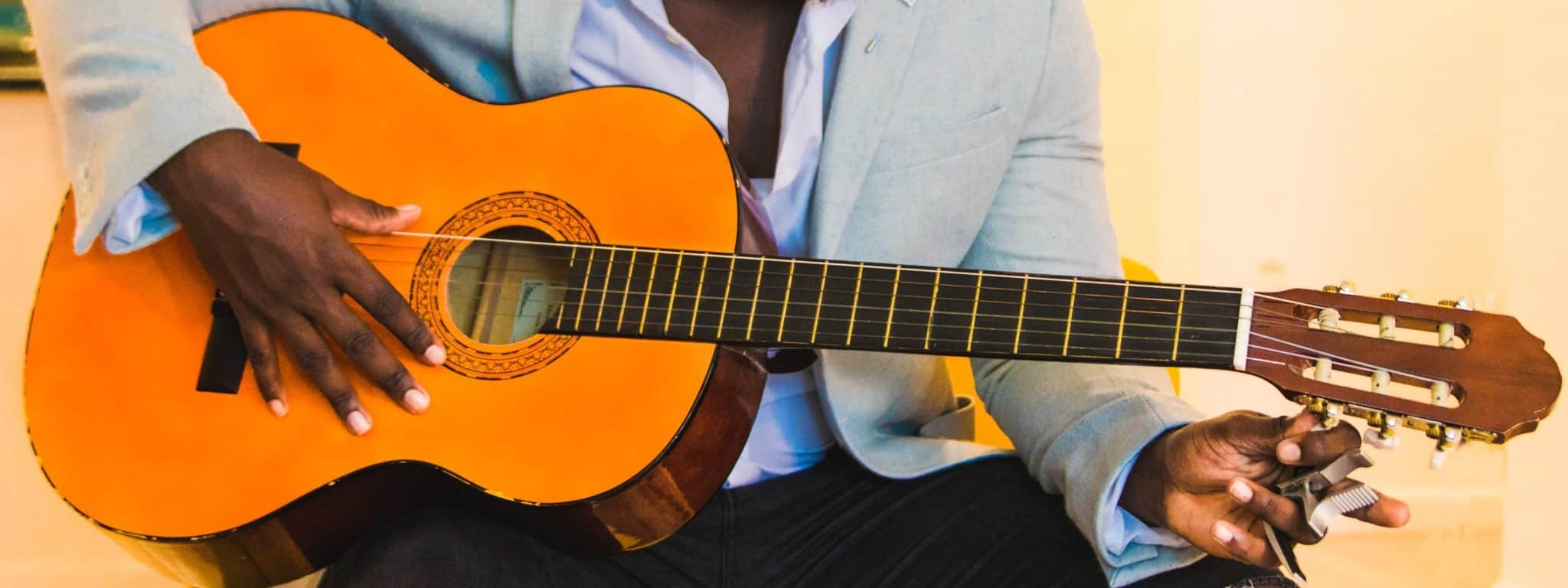 Man tuning an acoustic guitar